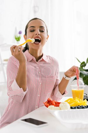 Photo for Happy woman eating tasty vegetable near orange juice and smartphone - Royalty Free Image