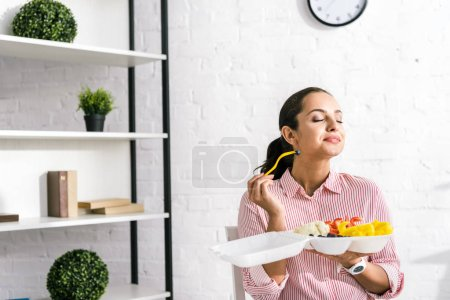 happy girl with closed eyes holding tasty vegetables in food container