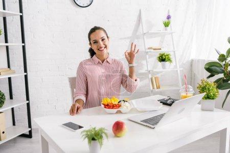 Photo pour Femme heureuse montrant ok signe près de légumes savoureux - image libre de droit