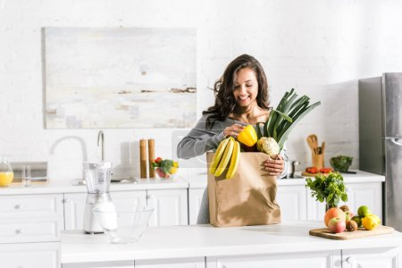 Photo for Happy woman standing near paper bag with tasty food - Royalty Free Image