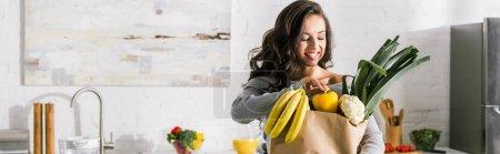 Panoramaaufnahme eines glücklichen Mädchens, das neben einer Papiertüte mit Lebensmitteln steht
