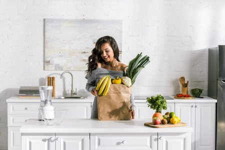 Photo for Cheerful woman standing near paper bag with tasty food - Royalty Free Image