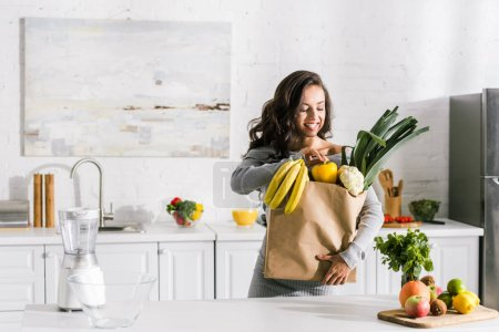 Photo for Cheerful girl standing near paper bag with tasty food - Royalty Free Image
