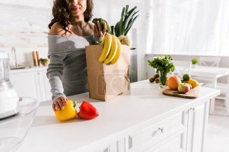 Photo pour Vue recadrée de femme restant près des épiceries dans la cuisine - image libre de droit