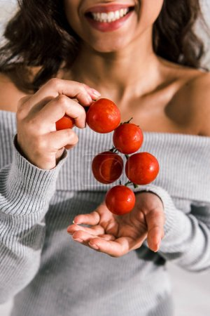 Photo for Cropped view of happy woman holding red and fresh cherry tomatoes - Royalty Free Image