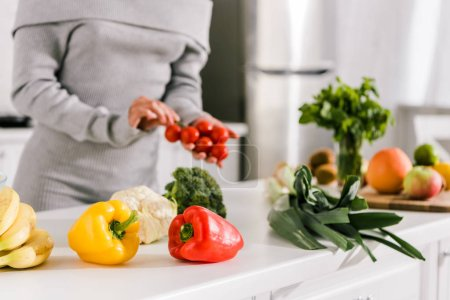 Photo for Selective focus of fresh vegetables near woman in kitchen - Royalty Free Image