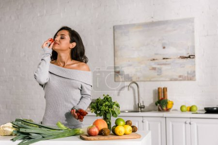 Photo for Attractive girl smelling cherry tomato near vegetables - Royalty Free Image
