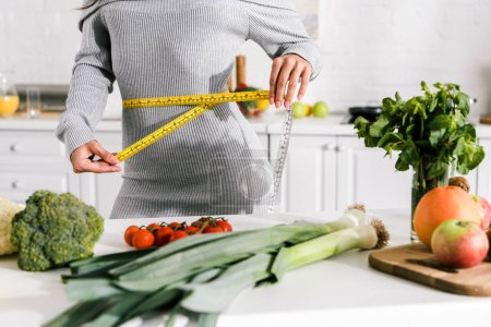Photo for Cropped view of woman measuring waist near vegetables on table - Royalty Free Image