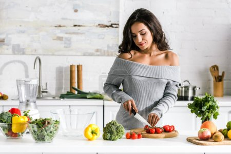 Photo for Attractive girl holding knife near cherry tomatoes - Royalty Free Image