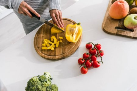 Photo for Cropped view of woman cutting paprika near vegetables - Royalty Free Image