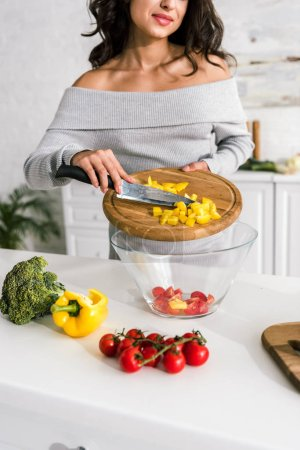Photo for Cropped view of woman putting sliced yellow paprika in glass bowl - Royalty Free Image