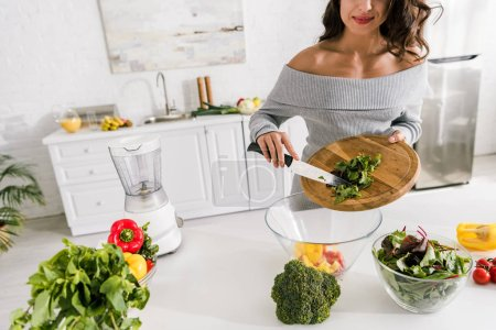Photo for Cropped view of girl holding cutting board near bowl with vegetables - Royalty Free Image