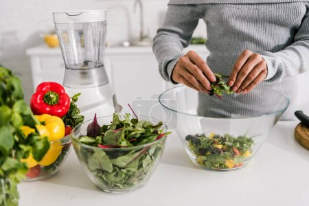 Photo for Cropped view of woman preparing salad in kitchen - Royalty Free Image