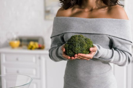 Photo for Cropped view of young woman holding green broccoli - Royalty Free Image