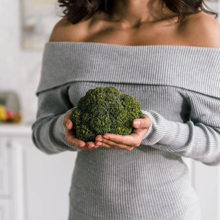Photo for Cropped view of young woman holding green and fresh broccoli - Royalty Free Image