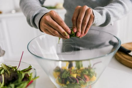 Photo for Cropped view of woman holding green leaves near glass bowl - Royalty Free Image