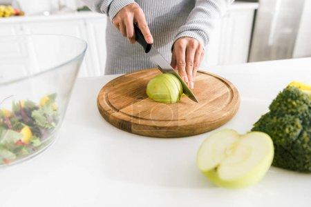 vista recortada de niña corte manzana verde cerca de cuenco de vidrio