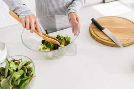 Photo for Cropped view of woman holding glass bowl with fresh salad - Royalty Free Image