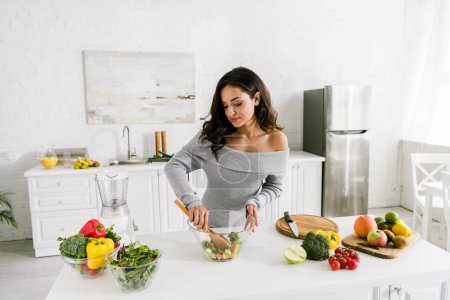 Photo for Attractive girl standing near bowls with salad and vegetables - Royalty Free Image