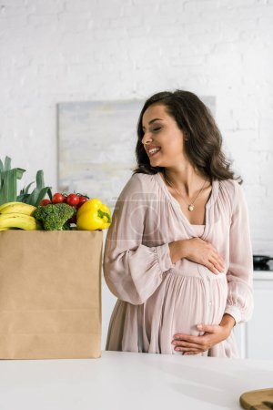 heureuse femme enceinte regardant sac en papier avec épicerie tout en touchant le ventre