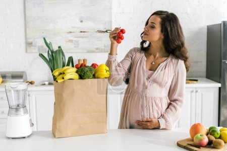 happy pregnant woman looking at cherry tomatoes near paper bag