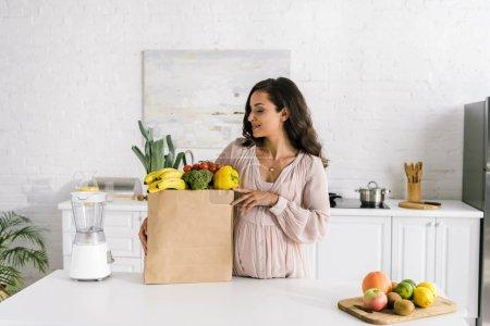 Photo pour Femme enceinte regardant le sac en papier avec des épiceries - image libre de droit
