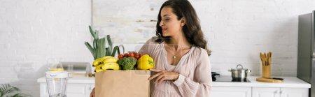 Photo pour Plan panoramique de la femme enceinte regardant sac en papier avec épicerie - image libre de droit