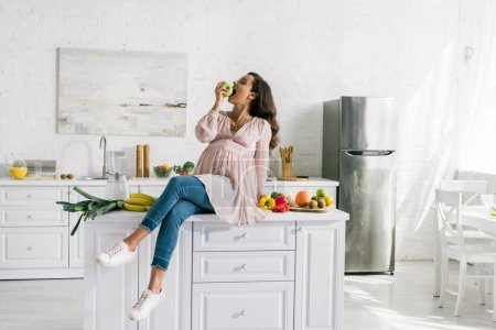 Photo for Happy pregnant woman eating apple near tasty food on table - Royalty Free Image