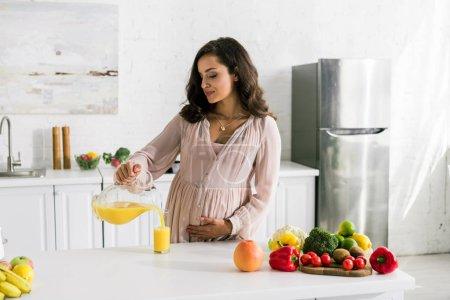 Photo pour Belle femme versant le jus d'orange dans le verre près des légumes - image libre de droit
