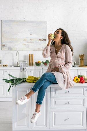 Photo pour Attrayant femme enceinte assis sur la table et manger de la pomme - image libre de droit