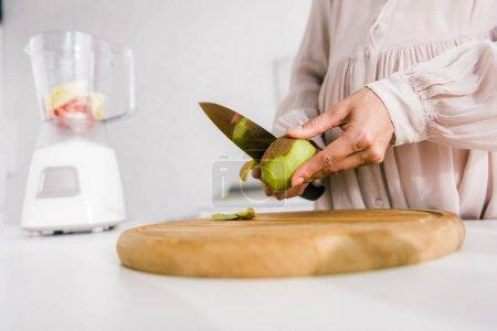 Photo for Selective focus of pregnant woman peeling kiwi - Royalty Free Image