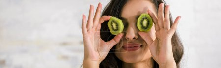 Photo for Panoramic shot of happy woman holding halves of kiwi fruit while covering eyes - Royalty Free Image