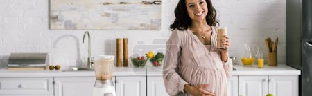 Photo for Panoramic shot of happy woman touching belly and holding tasty smoothie - Royalty Free Image