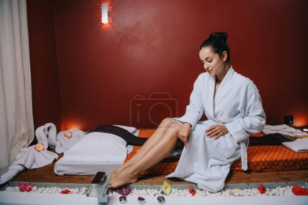 Photo pour Jolie femme en peignoir assis sur tapis de massage dans le salon de spa - image libre de droit