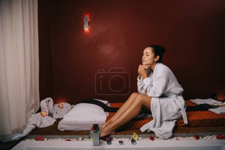 Photo for Attractive woman with closed eyes in bathrobe sitting on massage mat in spa salon - Royalty Free Image