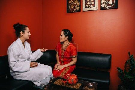 Photo pour Souriant femme et asiatique masseur assis sur canapé et parler dans spa - image libre de droit