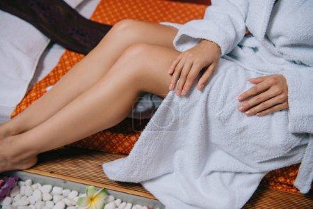 Photo pour Vue recadrée de femme dans le peignoir s'asseyant sur le tapis de massage dans le salon de spa - image libre de droit
