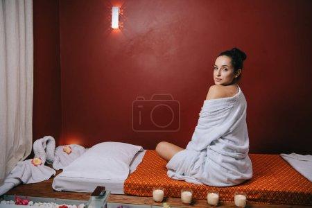 Photo pour Femme attirante dans le peignoir s'asseyant sur le tapis de massage dans le salon de spa - image libre de droit