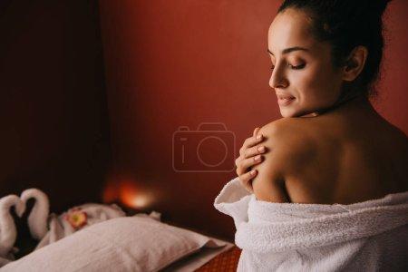 Photo pour Jolie femme avec les yeux fermés en peignoir dans le salon de spa - image libre de droit