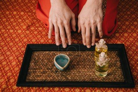 Photo pour Vue recadrée de masseur avec des huiles de parfum dans des bouteilles et un bol - image libre de droit