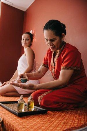 Photo pour Mise au point sélective de masseur asiatique versant l'huile de parfum sur la main - image libre de droit