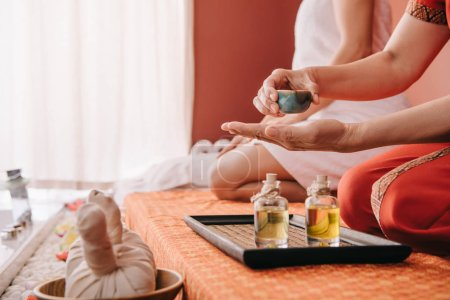 Photo for Cropped view of masseur pouring fragrance oil on hand - Royalty Free Image