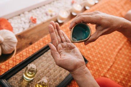 Photo pour Vue recadrée de masseur versant l'huile de parfum sur la main - image libre de droit