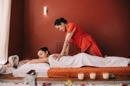 Photo pour Masseur asiatique faisant le massage de dos à la femme attirante dans le salon de spa - image libre de droit