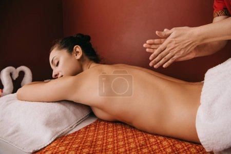 Photo pour Vue recadrée du masseur appliquant l'huile de parfum et la femme se trouvant sur le tapis de massage - image libre de droit