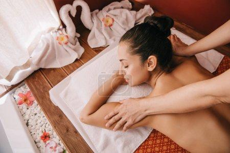 Photo pour Vue recadrée du masseur faisant le massage d'épaule à la femme sur le tapis de massage - image libre de droit