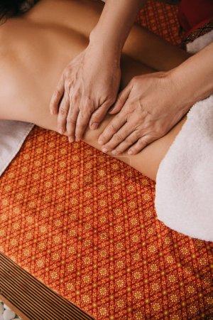 Photo pour Vue recadrée de masseur faisant le massage de dos à la femme sur le tapis de massage - image libre de droit