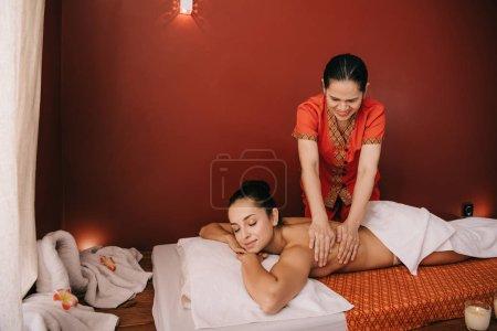 Photo pour Asiatique masseur faire retour massage à femme sur massage tapis - image libre de droit