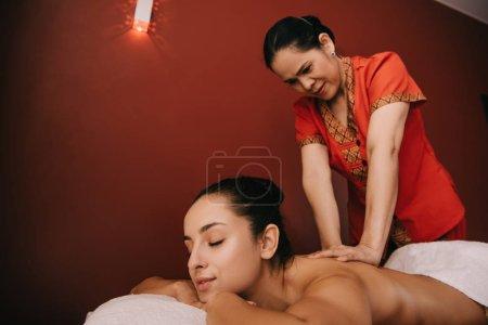 Photo pour Masseur asiatique faisant le massage de dos à la femme sur le tapis de massage - image libre de droit
