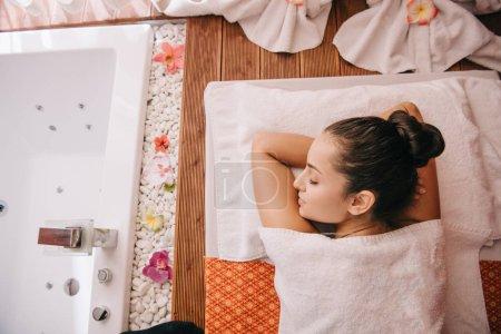 Photo pour Vue supérieure de la femme attirante avec les yeux fermés se trouvant sur le tapis de massage - image libre de droit